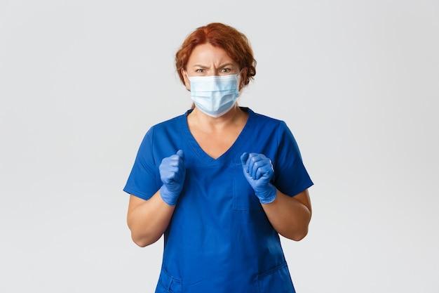 Trabalhadores médicos, pandemia de covid-19, conceito de coronavírus. retrato de enfermeira enojada, médica de meia-idade com máscara médica e luvas fazendo careta de aversão, vendo algo desagradável ou desagradável.
