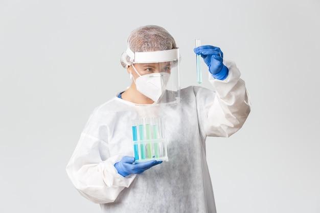 Trabalhadores médicos, pandemia de covid-19, conceito de coronavírus. retrato de médica profissional em equipamentos de proteção individual ppe, olhando para tubo de ensaio com vacina, sorrindo satisfeito, pesquisando.