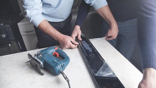 Trabalhadores medindo e cortando bancadas de cozinha com serra elétrica.