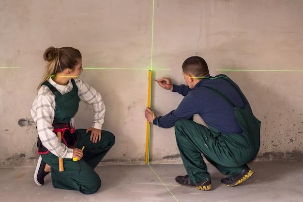 Trabalhadores medindo paredes com ferramenta de nível a laser