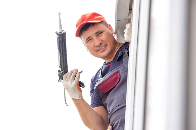 Trabalhadores mestres instalam conserto de peitoril de janela na construção de casas asiáticas coladas com silicone