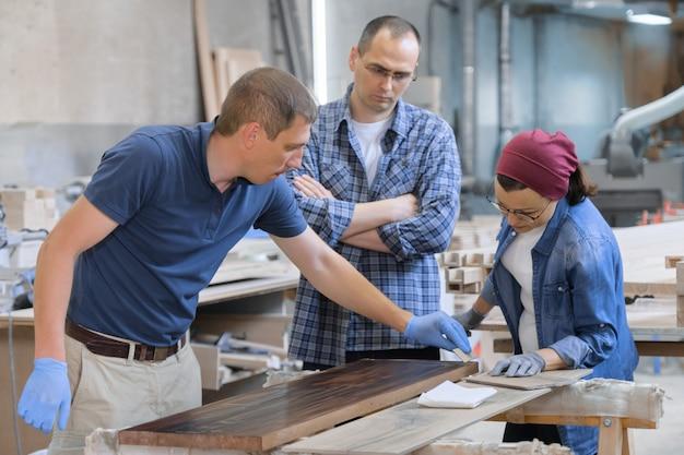 Trabalhadores na oficina de carpintaria para carpintaria, envernizando a prancha de madeira com óleo