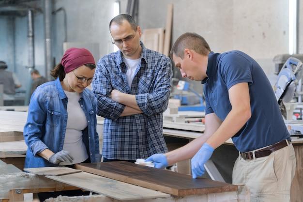 Trabalhadores na oficina de carpintaria para madeira, envernizando a prancha de madeira com óleo