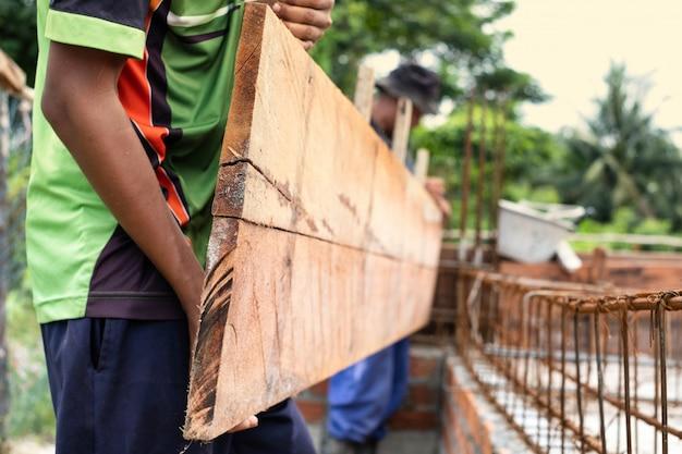 Trabalhadores, pegando a prancha para configurar para feixe de casa, construção de casa