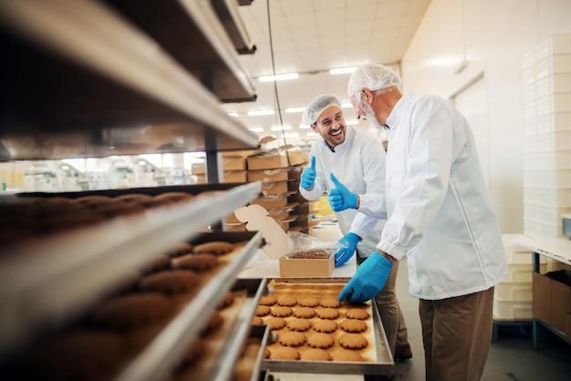 Trabalhadores que embalam biscoitos em caixas enquanto estão na fábrica de alimentos.