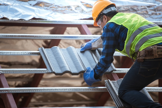 Trabalhadores que instalam telhados vestindo roupas de segurança construção de uma indústria de telhados, ladrilhos cerâmicos ou cpac