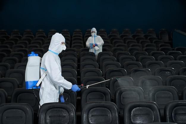 Trabalhadores que limpam a sala do cinema com desinfetantes especiais.