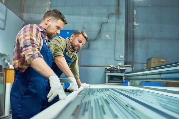 Trabalhadores que operam a máquina de gravação a laser