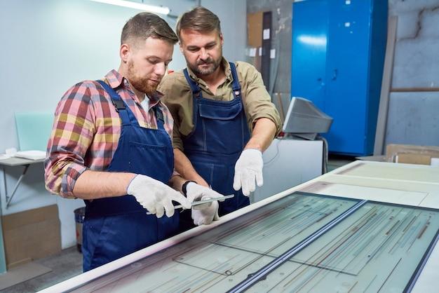 Trabalhadores que operam a máquina de gravura em vidro