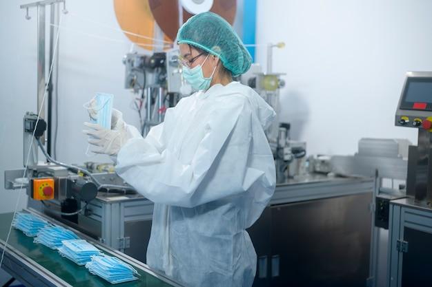 Trabalhadores que produzem máscara cirúrgica em fábrica moderna, proteção covid-19 e conceito médico.
