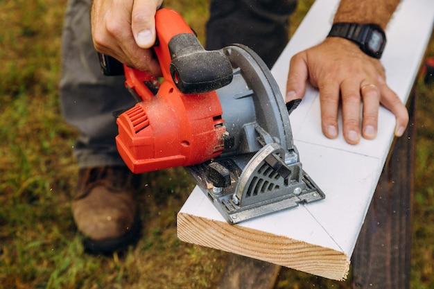 Trabalhadores que usam serras de corte para serrar construção industrial
