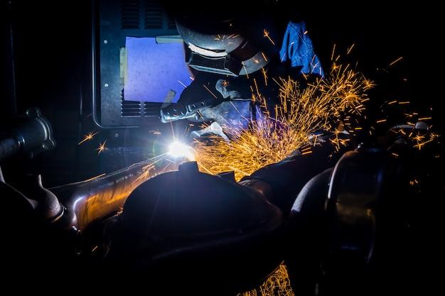 Trabalhadores são grooving com fios de solda de carbono com faíscas