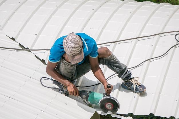 Trabalhadores são vistos um telhado