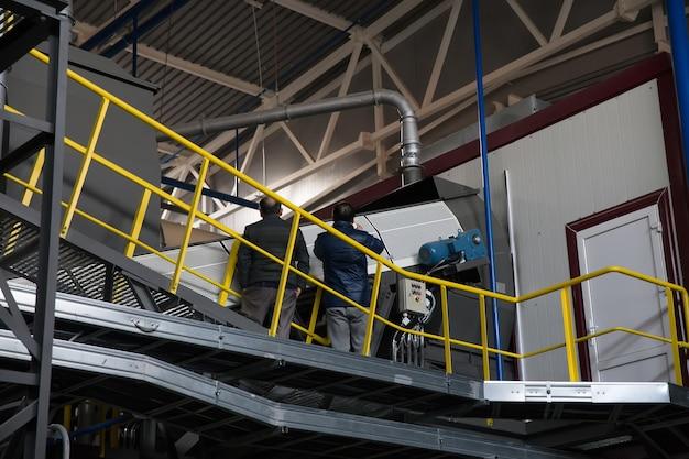 Trabalhadores servem o transportador na fábrica para processamento de lixo doméstico