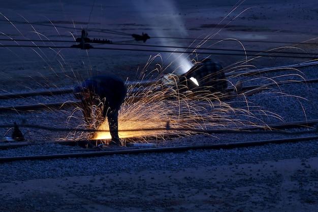 Trabalhadores, soldadores, consertam trilhos de metal. indústria e reparo de centros de transporte