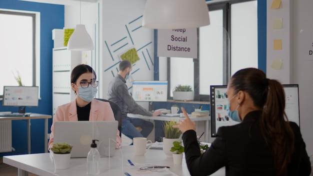 Trabalhadores usando máscara protetora, falando sobre projeto de negócios, digitando no pc no escritório durante a pandemia global de coronavírus. trabalho em equipe em startup mantém distanciamento social