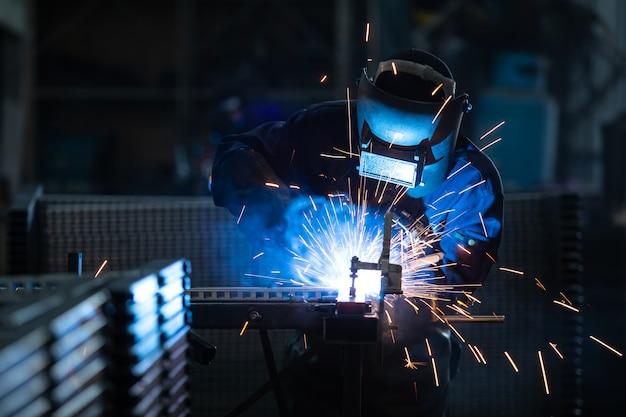 Trabalhadores vestindo uniformes industriais e soldada iron mask em plantas de soldagem de aço.