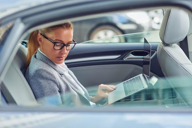 Trabalhando a caminho da reunião de negócios, vista lateral de uma ocupada empresária de meia-idade usando um laptop