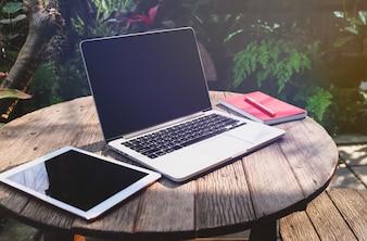Trabalhando ao ar livre com laptop e tablet em cima da mesa no jardim