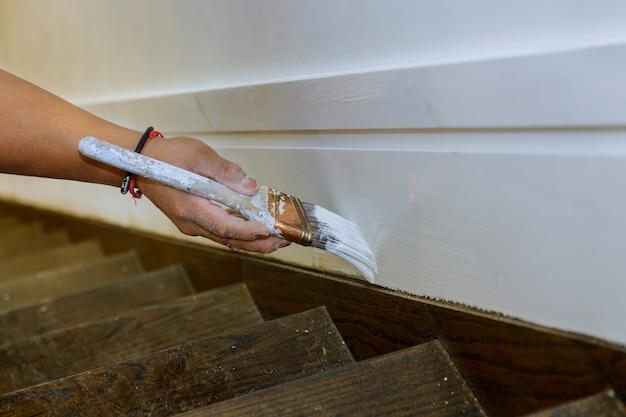 Trabalhando com as mãos de um pintor empreiteiro com a pintura da moldura de madeira nas escadas com pincel