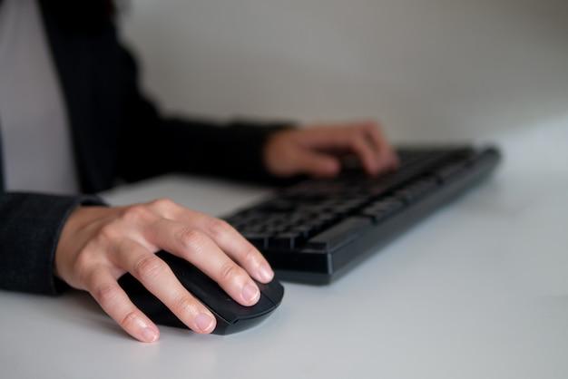 Trabalhando com as mãos no mouse e teclado no conceito de negócios e educação
