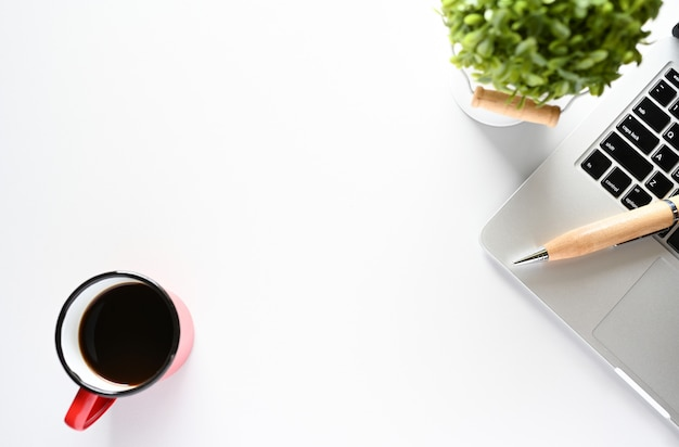 Trabalhando com computador portátil e planta e café cópia espaço na mesa moderna