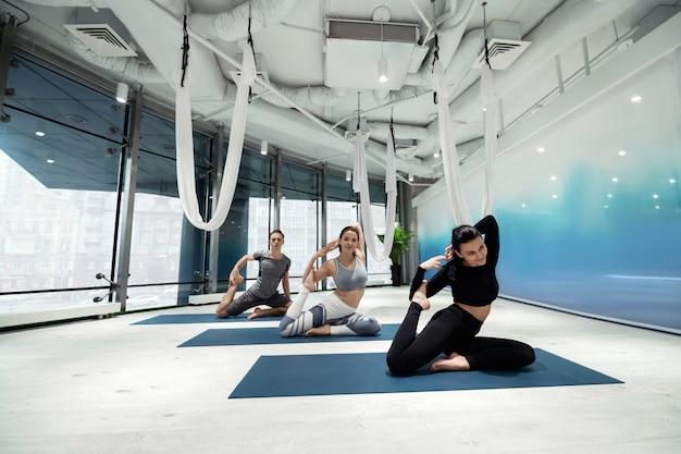 Trabalhando com flexibilidade. duas mulheres ativas e em forma e um homem trabalhando na flexibilidade enquanto fazem ioga