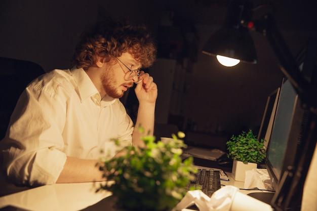 Trabalhando com gráficos. homem trabalhando sozinho no escritório durante a quarentena de covid-19, permanecendo até tarde da noite. jovem empresário, gerente fazendo tarefas com smartphone, laptop, tablet no espaço de trabalho vazio.