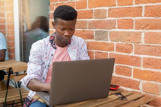Trabalhando com laptop homem africano contra o fundo da parede de tijolos