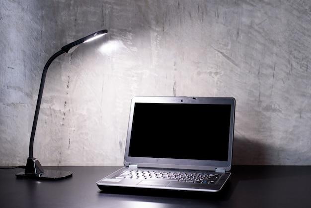 Trabalhando com laptop preto e lâmpada led branca na mesa preta