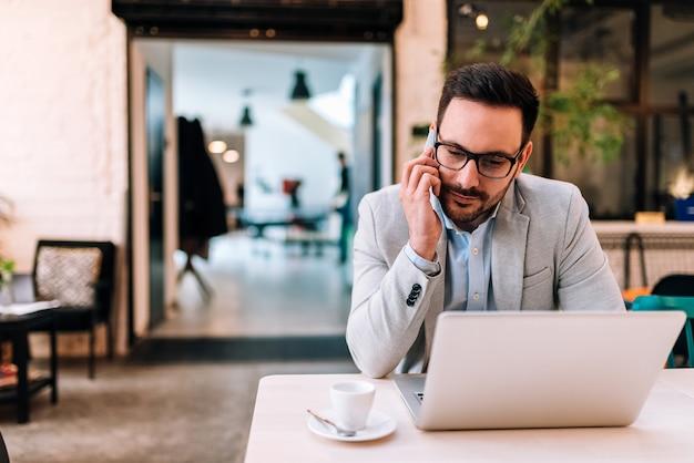 Trabalhando com prazer. homem novo que fala no telefone móvel e que olha seu portátil ao sentar-se no café.