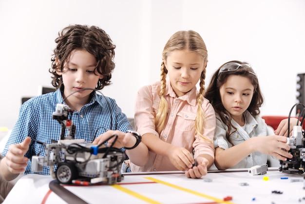 Trabalhando com sistema de controle. o criativo envolveu crianças curiosas sentadas na aula e usando um robô enquanto trabalhavam no projeto de tecnologia