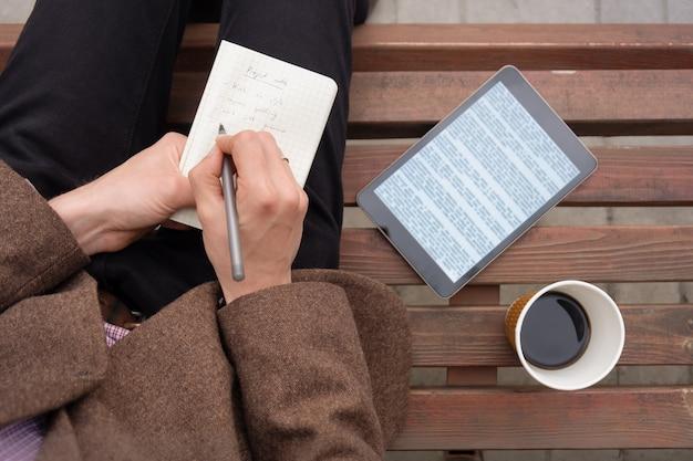 Trabalhando com texto fora da cidade com bloco de notas e tablet