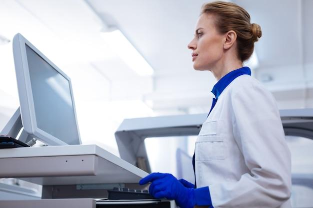 Trabalhando duro. ângulo baixo de uma agradável cientista feminina focada olhando para a tela de mãos dadas perto do teclado em pé no laboratório