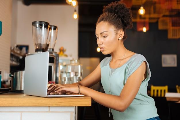Trabalhando duro. linda freelancer encaracolada usando uma blusa bonita e estilosa, trabalhando duro usando seu laptop