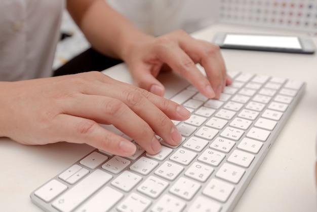 Trabalhando em casa escritório mão no teclado
