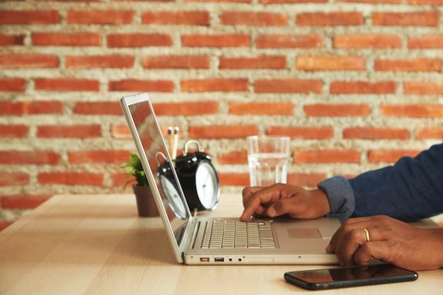 Trabalhando em casa, perto de mãos de homem digitando em um teclado de laptop na mesa com a luz do sol