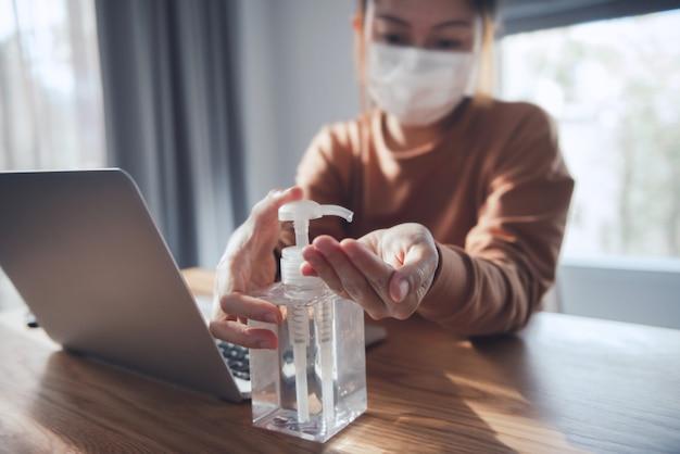 Trabalhando em casa, proteção contra vírus corona, closeup limpando as mãos com gel desinfetante, mulher em quarentena por coronavírus usando máscara protetora.