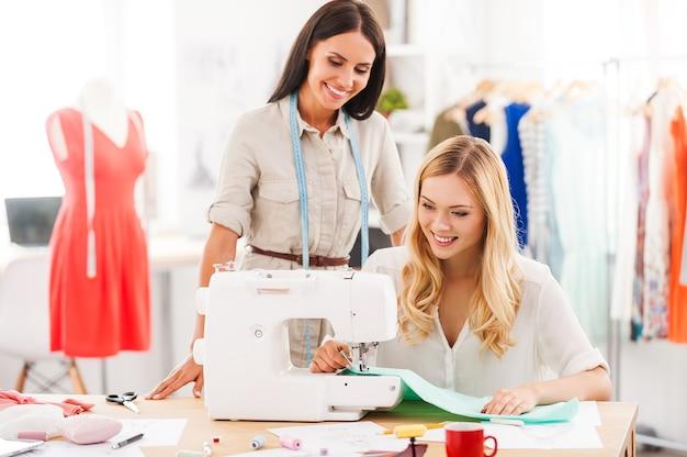 Trabalhando em novos estilos de moda. duas jovens felizes costurando juntas em sua oficina de moda