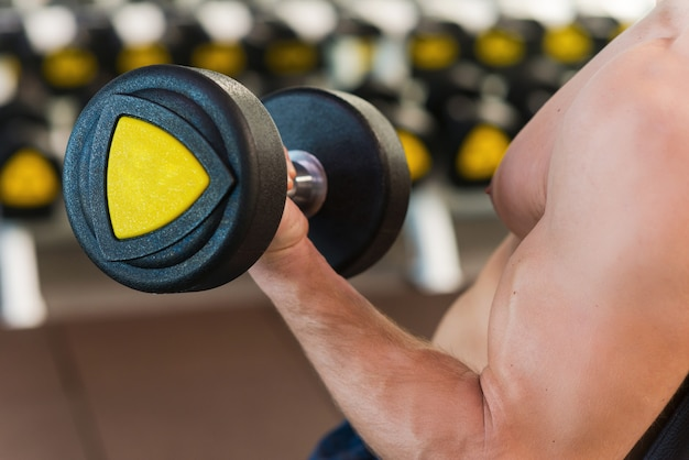 Trabalhando em seu bíceps perfeito. close de um homem musculoso trabalhando no bíceps enquanto se exercita com halteres na academia