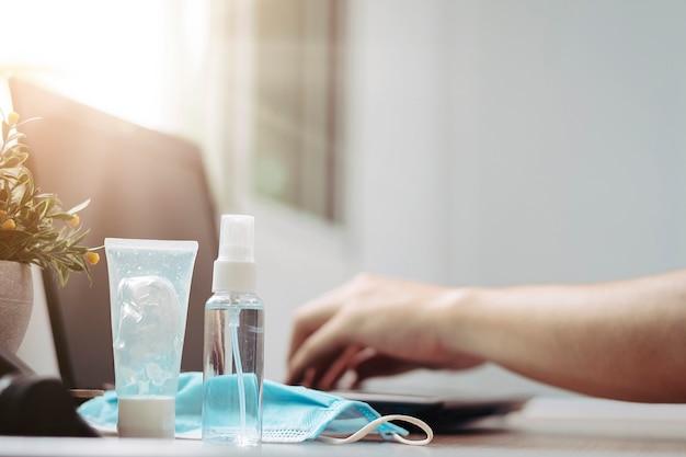 Trabalhando em suas mesas em casa gel desinfetante para as mãos com conceito de prevenção de máscaras cirúrgicas médicas