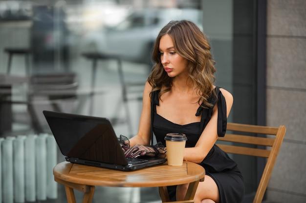 Trabalhando em um laptop, linda mulher com um vestido em um café de verão