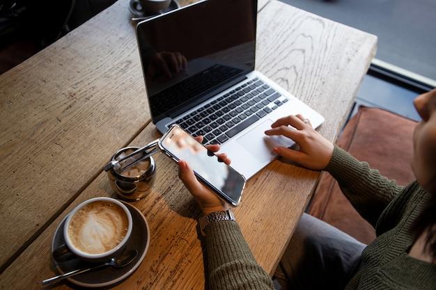 Trabalhando em uma cafeteria. mulher jovem olhando casual trabalha no laptop na cafeteria.