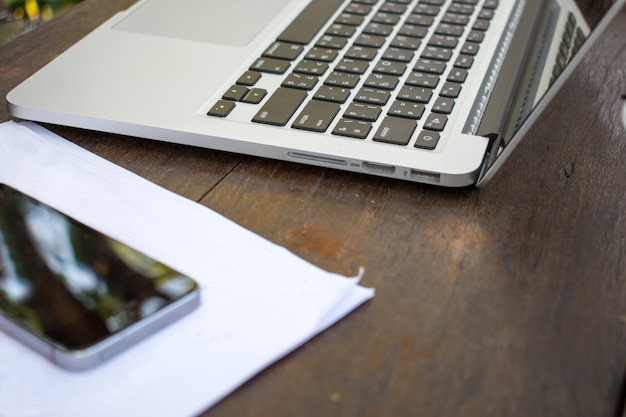 Trabalhando fora. inclui computador, telefone, papel e colocado sobre uma mesa de madeira velha.