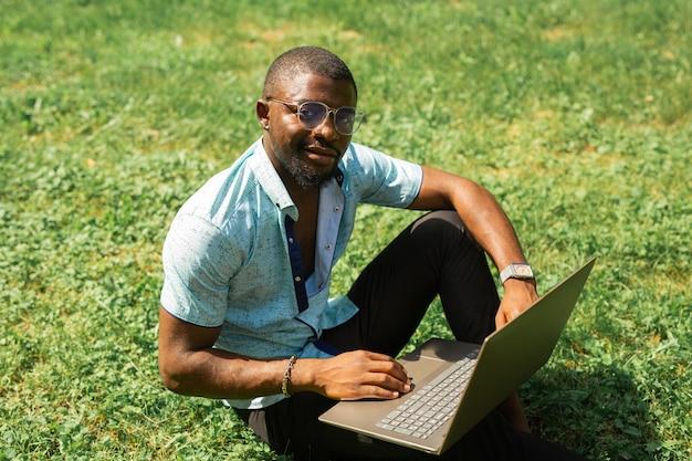 Trabalhando homem africano com laptop na grama no verão