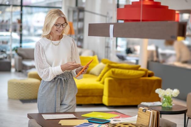 Trabalhando, humor. designer de mulher loira de óculos com jóias no pescoço, em pé perto da mesa com um tablet nas mãos, olhando para a tela sorrindo.