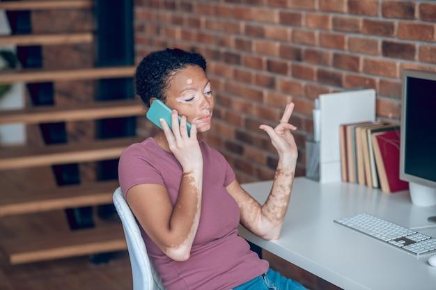 Trabalhando. jovem afro-americana falando ao telefone e parecendo ocupada