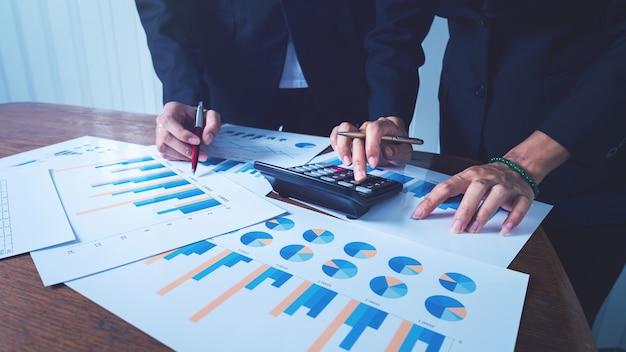 Trabalhando junto com mulheres de negócios com gráficos financeiros e gráficos com calculadora para cálculo de dados e gerenciamento.