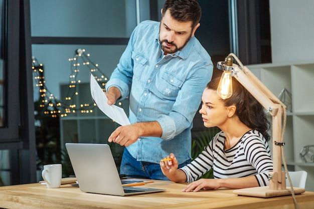 Trabalhando juntos. homem bonito e inteligente perto de sua colega e apontando para a tela do laptop enquanto trabalhava com ela