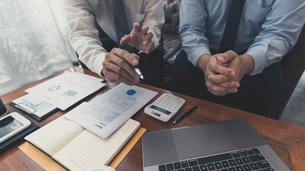 Trabalhando juntos no conceito de escritório, jovens empresários discutem a situação do mercado